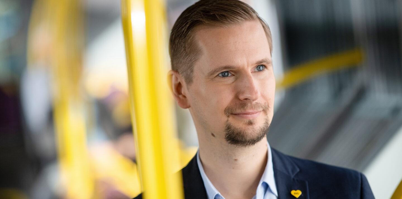 Ein junger Mann steht in einem BVG-Fahrzeug neben einer gelben Haltestange.