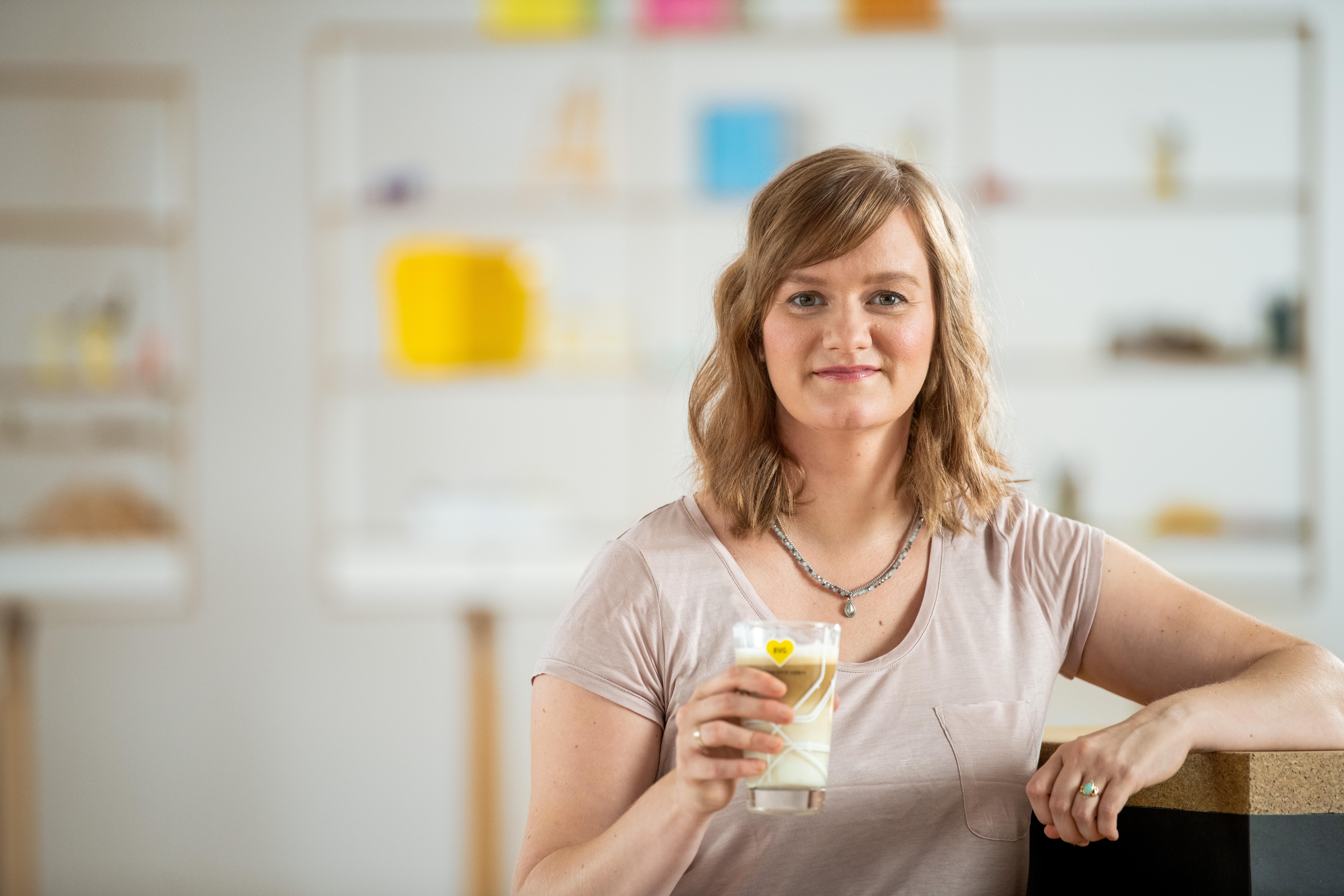 IT-Mitarbeiterin Antje genießt in der Pause einen Latte-Macchiato aus einem schönen BVG-Glas.