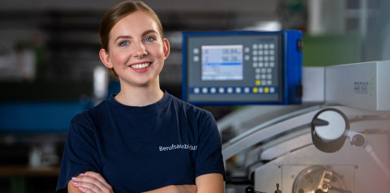 Nele absolviert ihre Ausbildung in Berlin bei der BVG: Sie steht in einer Werkstatt und lächelt.
