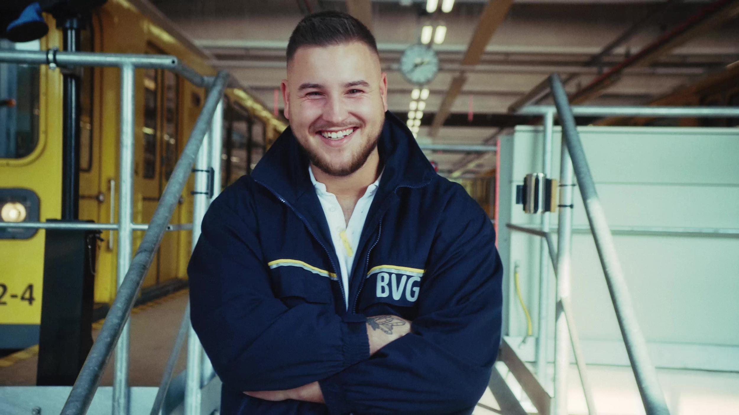 Ein junger BVG-Mitarbeiter steht in Arbeitskleidung lächelnd auf einer Treppe. Seitlich hinter ihm ist ein BVG-Fahrzeug zu erkennen.