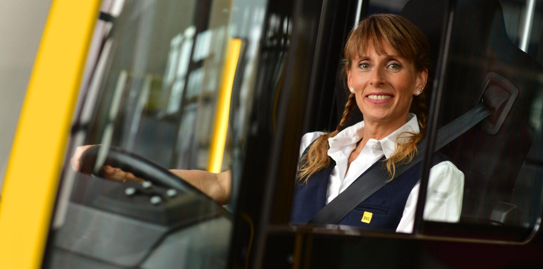 Busfahrer in Berlin werden: Manuela sitzt am Steuer eines BVG-Busses. Sie lächelt und blickt durch die Glasscheibe. Sie ist Busfahrerin bei der BVG.