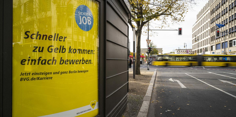 Im Vordergrund ist eine gelbe BVG-Außenwerbung zum Thema Karriere zu sehen, während im Hintergrund ein gelber BVG-Bus über die Kreuzung fährt.