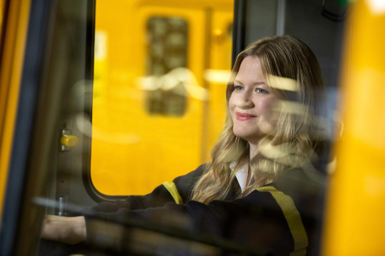 Anna ist U-Bahnfahrerin in Berlin bei der BVG. Sie schaut aus der U-Bahn heraus, während im Hintergrund ein weiteres Fahrzeug zu sehen ist.
