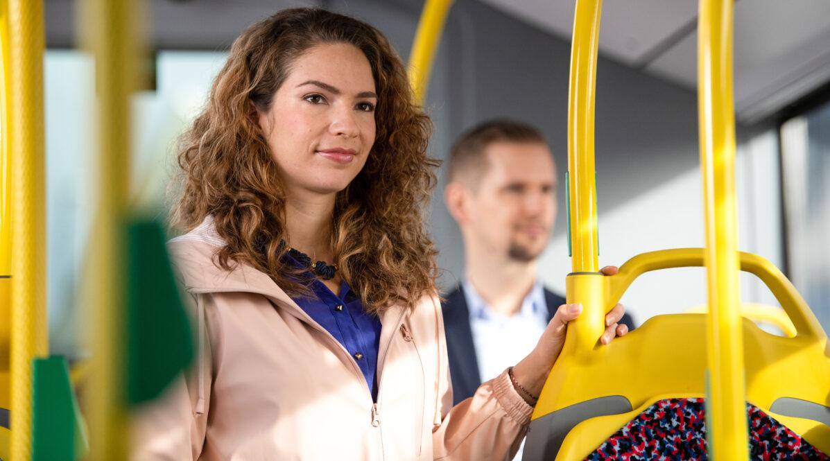 Eine junge Frau steht in einem BVG-Bus, hinter ihr ist ein junger Mann zu erkennen.