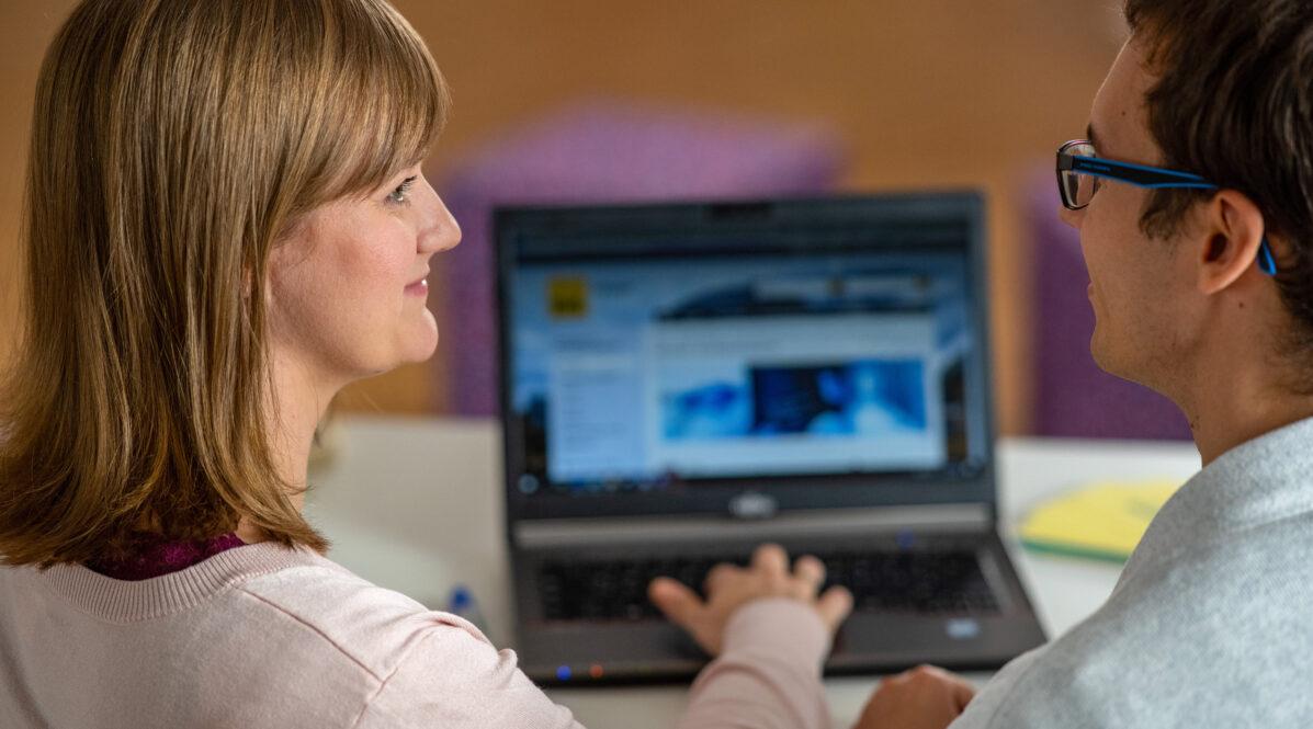 IT-Mitarbeiterin Antje und ihr Kollege aus der IT der BVG sitzen zusammen vor einem Laptop.
