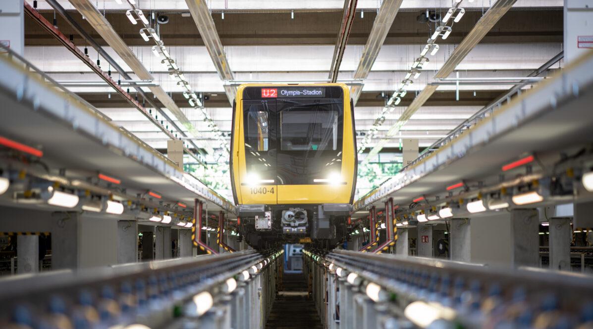 Bild aus einer BVG-Werkstatt: Eine U-Bahn ist zur Wartung aufgebockt. Ihre Scheinwerfer strahlen durch die Werkstatt.