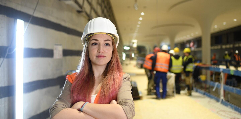 Ingenieurin Svenja steht mit verschränkten Armen auf einer Baustelle. Hinter ihr sind ihre Kolleg*innen in Schutzkleidung zu sehen.
