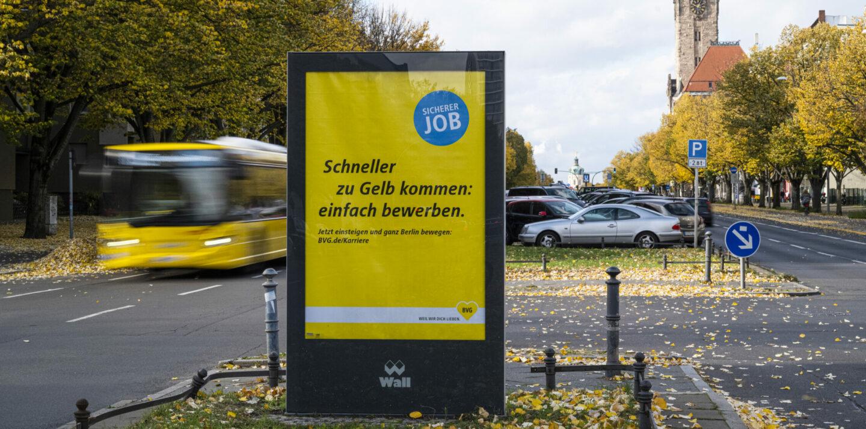 In der Mittelinsel einer Straße steht eine Außenwerbung für BVG-Karriere. Im Hintergrund steht ein gelber BVG-Bus.