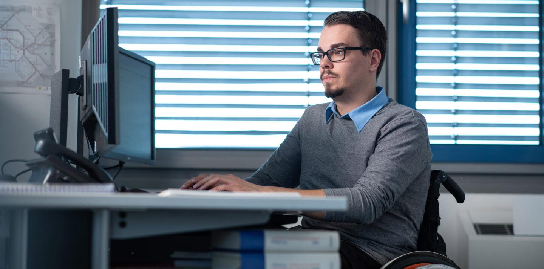 Marcel arbeitet als Kaufmann bei der BVG und sitzt in seinem Rollstuhl am Arbeitsplatz.
