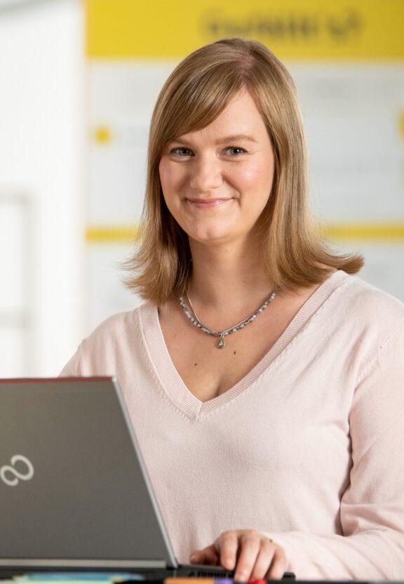 IT-Mitarbeiterin Antje steht in ihrem BVG-Büro am Laptop und arbeitet.