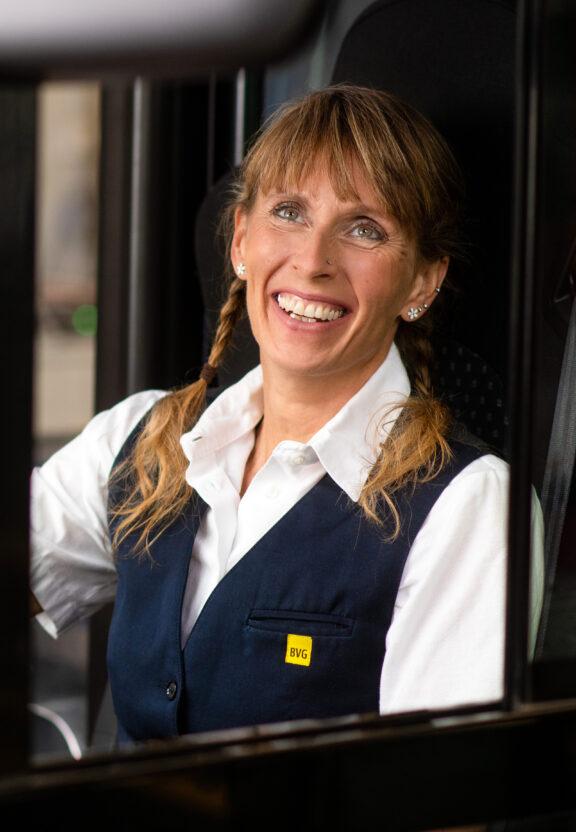 Busfahrerin Manuela sitzt am Steuer eines BVG-Busses und schaut lächelnd durch die Glasscheibe.