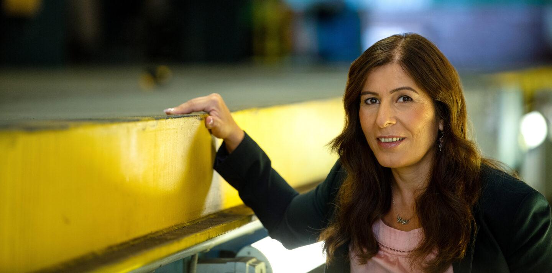 BVG-Bauingenieurin Tülay steht vor einem verschwommenen Hintergrund und lächelt in die Kamera.