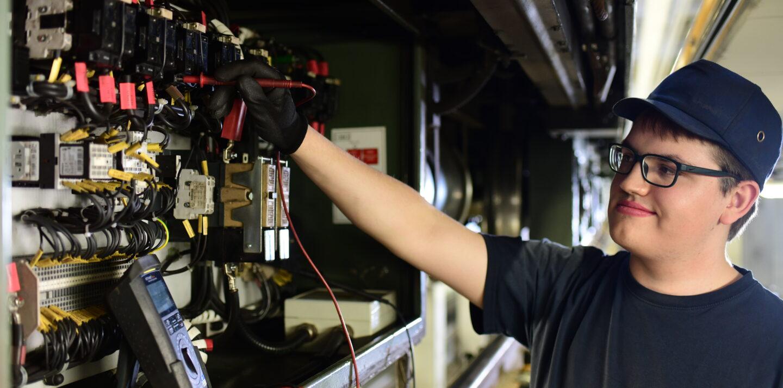 Ein junger Mann absolviert sein Praktikum in Berlin bei der BVG in einer Werkstatt. Er arbeitet an einer Oberfläche mit elektronischen Elementen.