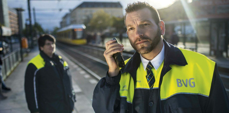 Eine Kollegin und ein Kollege aus dem Bereich Sicherheitsdienst stehen in Schutzkleidung mit Funkgerät am Bahnsteig der Straßenbahn.