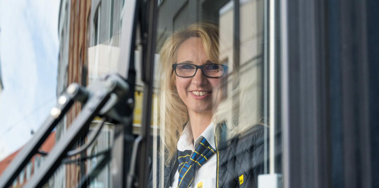 Anett ist Straßenbahnfahrerin bei der BVG. Sie sitzt lächelnd hinter dem Steuer einer Tram.