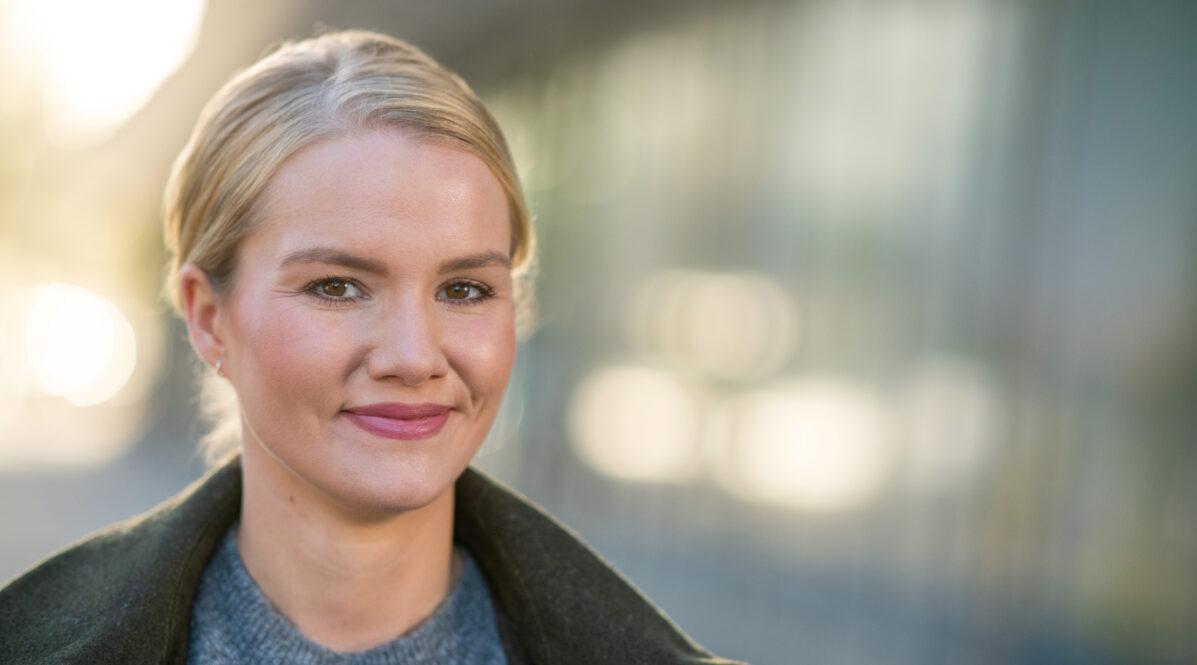 Eine junge, blonde Frau lächelt in die Kamera. Sie steht draußen vor einem verschwommenen Hintergrund.