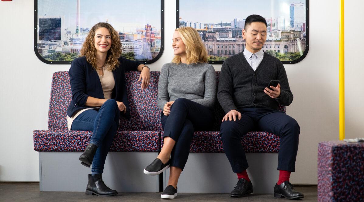 Drei junge BVGer sitzen nebeneinander in einem Warteraum der BVG und unterhalten sich.