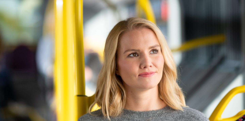 Eine blonde Frau sitzt in einem BVG-Bus. Sie schaut aus dem Fenster.