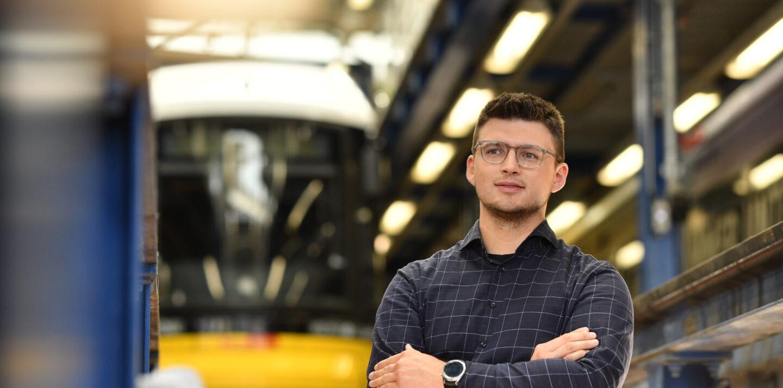 Ein junger BVG-Mitarbeiter steht in einer Werkstatt-Halle. Im Hintergrund ist eine Straßenbahn zu erkennen.