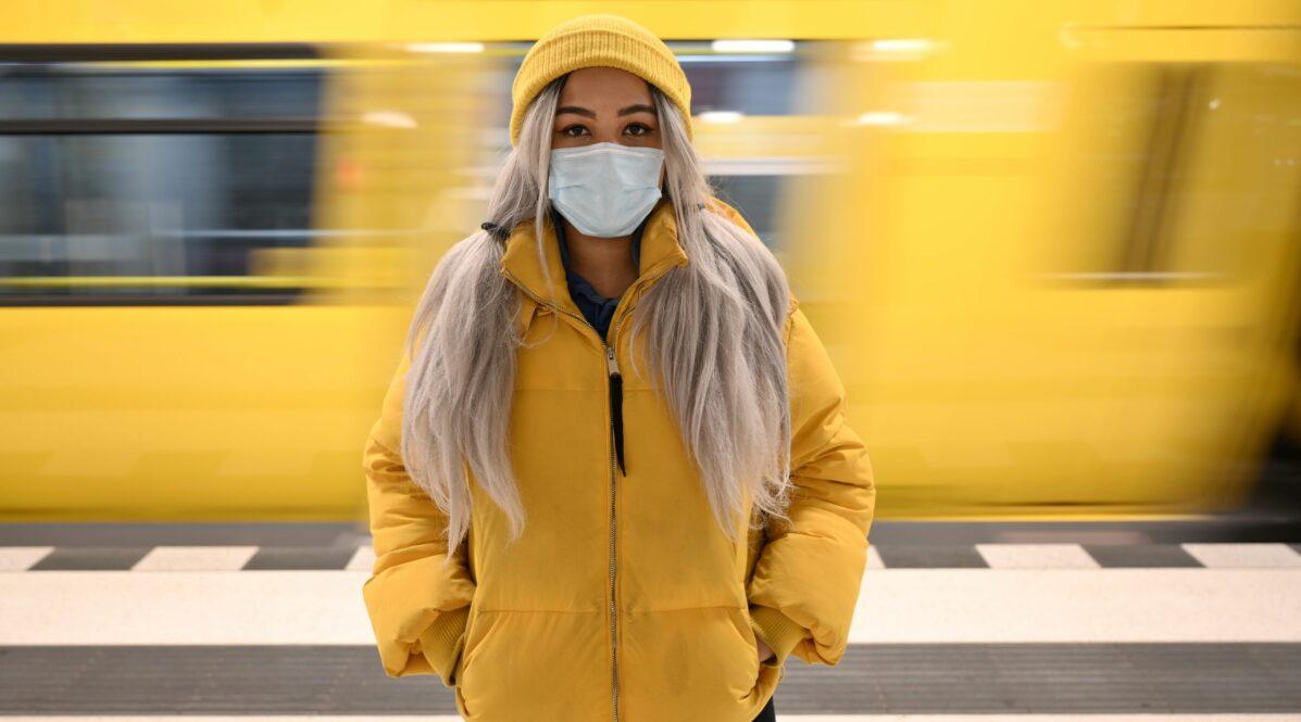 Eine Frau mit Maske und gelber Regenjacke steht im U-Bahnhof. Hinter ihr fährt eine U-Bahn ein.