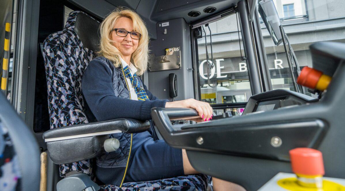 BVG-Straßenbahnfahrerin Anett Schemkowski sitzt in Uniform in der Fahrer*innenkabine einer Straßenbahn und steuert das Fahrzeug.