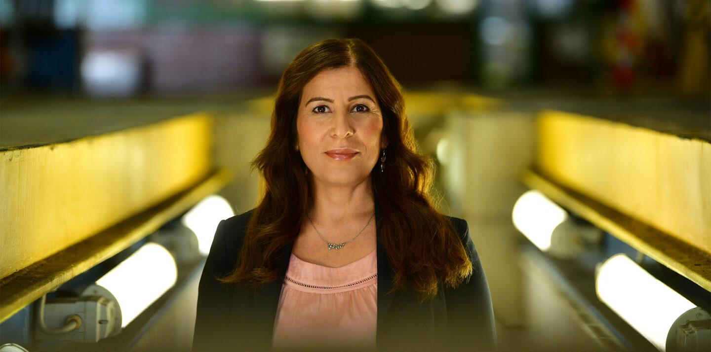 Portraitaufnahme einer Frau mit Blazer, die in einer BVG-Werkstatt in einer von Neonlampen beleuchteten Arbeitsgrube steht.