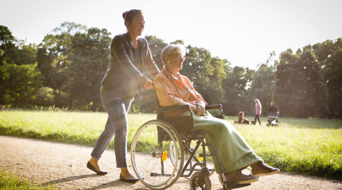 Eine junge Frau fährt eine ältere Dame im Rollstuhl durch den Park spazieren
