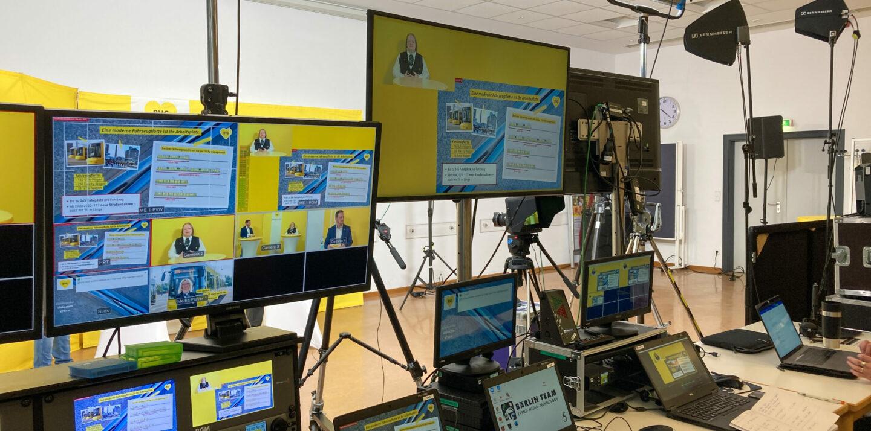 Das Bild zeigt mehrere Bildschirme in verschiedenen Größen. Auf den Bildschirmen ist ein digitales Event zu sehen