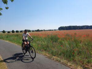 Isabel auf ihrem privaten Fahrrad unterwegs. Im Hintergrund sieht man ein Mohnblumenfeld.