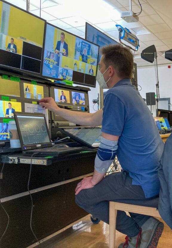 Ein Mitarbeiter führt Regie beim digitalen Event im Sendestudio.