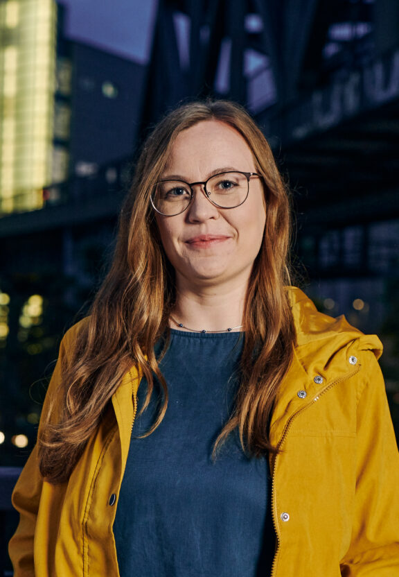 BVG-Projektleiterin Jennifer steht vor BVG-Gebäude. Sie trägt eine gelbe Jacke.