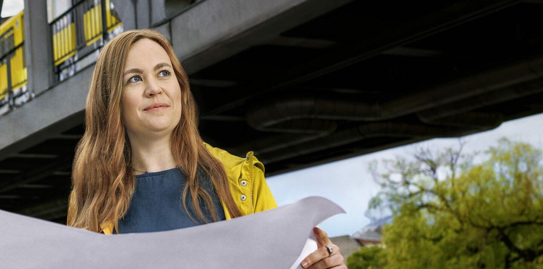 Jennifer steht unter einem U-Bahn Viadukt und hält einen Bauplan in der Hand. Sie blickt in die Ferne.