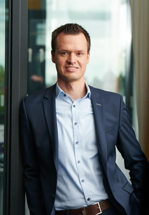 Thomas steht in einem Anzug vor einem Bürogebäude der BVG