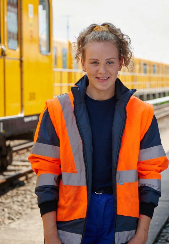 Azubi Ronja steht in Arbeitskleidung und Warnweste vor einer U-Bahn neben den Gleisen