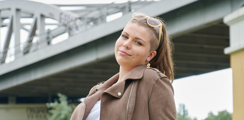 Auszubildende Michelle sitzt im Park vor einem U-Bahnaquädukt
